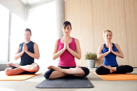 Three people meditating in a yoga class