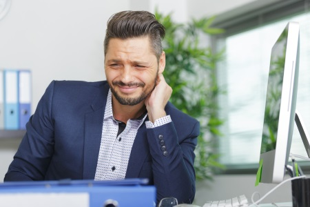 Man sat at desk suffering with neck pain