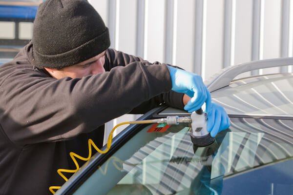 Man repairing crack in Windscreen