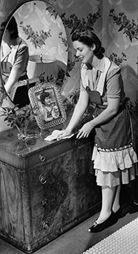 Black and White photo of maid polishing wooden furniture