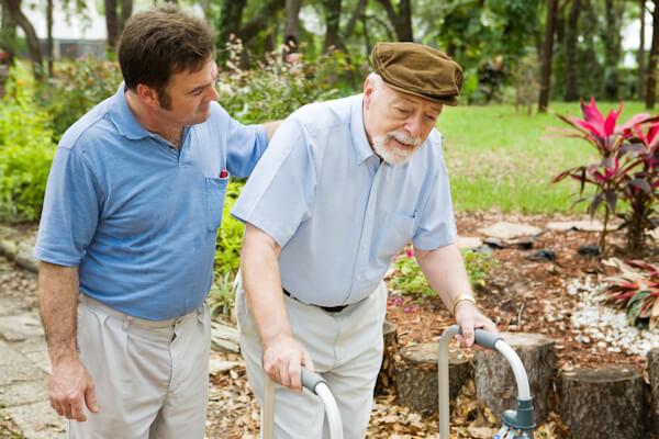 Carer walking with Elderly Man