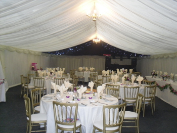 room decorated for a wedding, with chairs and table set up for a meal
