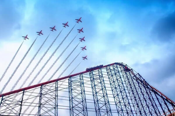 Red Arrows flying over one of Blackpool Pleasure Beach's roller coasters