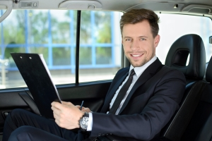 Smiling business man riding in the back of a taxi