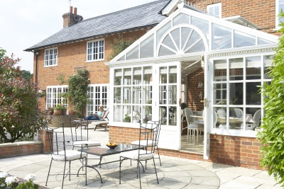 Table with chairs on garden patio with conservatory and house in background
