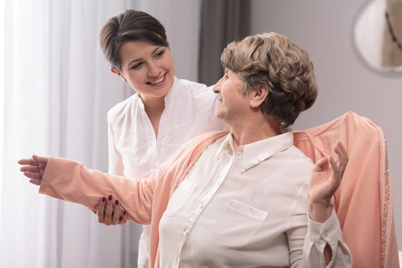 Carer putting on a cardigan for a old woman