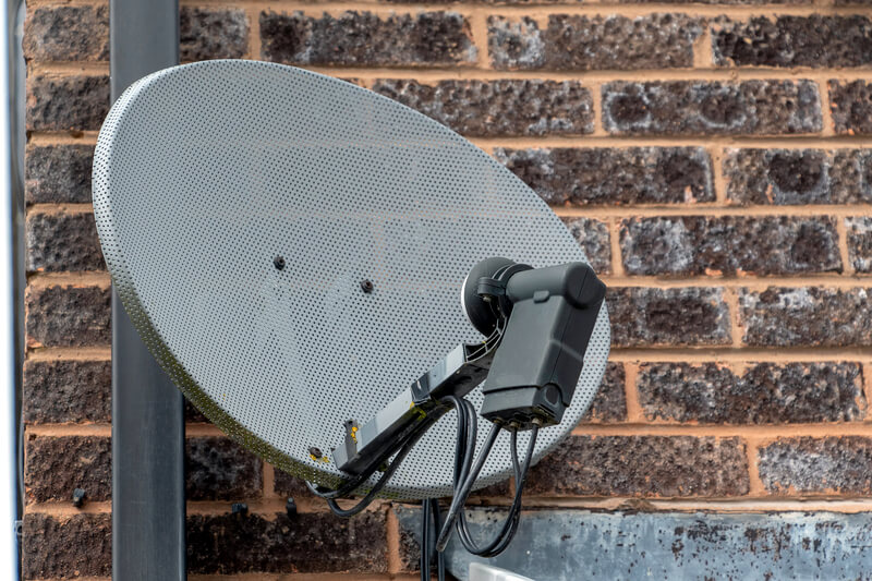 TV satellite installed on brick wall of house