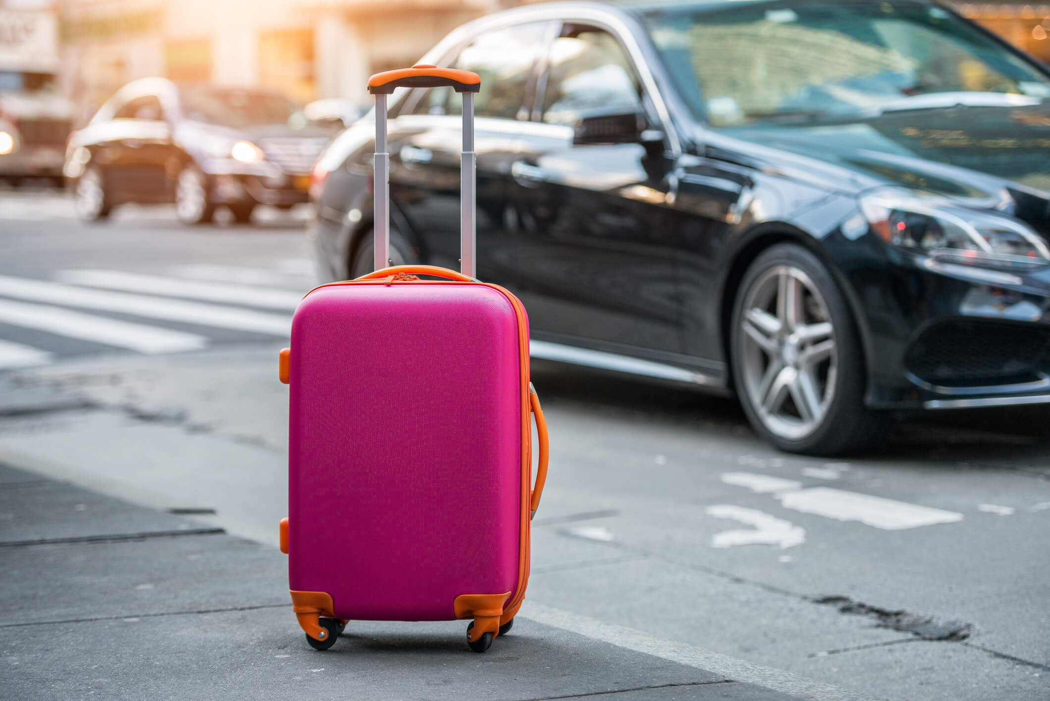 Suitcase in front of car.