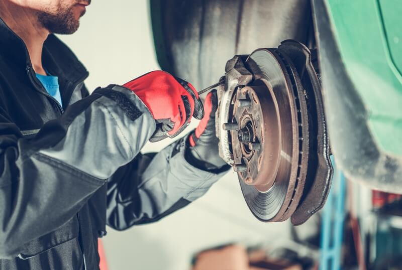 mechanic replacing the brakes of a car