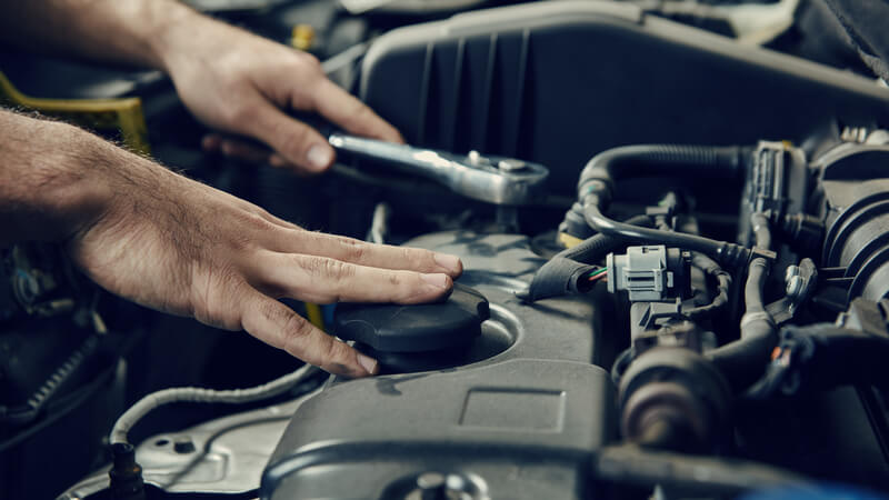 Car engine oil being checked
