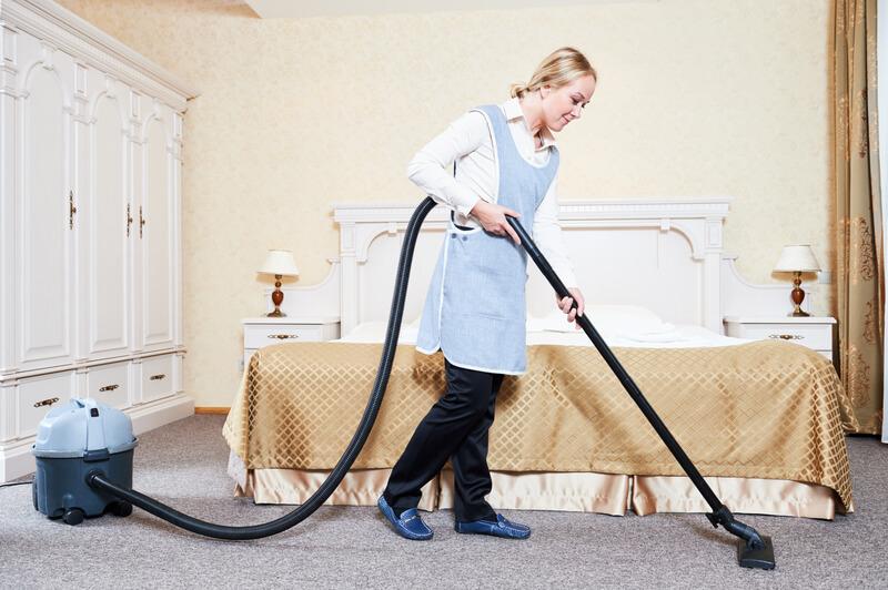 Female housekeeping worker with vacuum cleaner