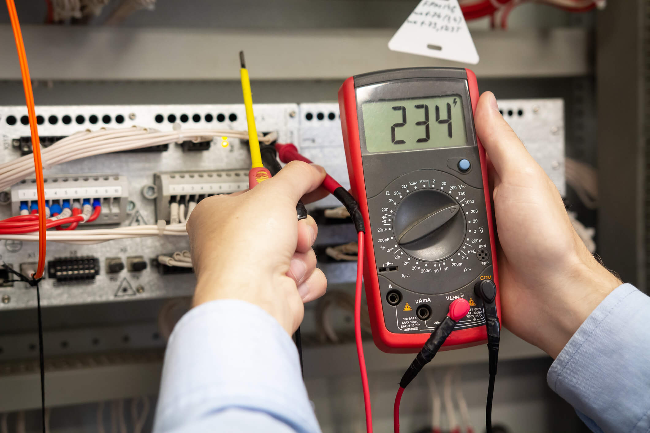 Electrician adjusts electrical control panel on power station, using tester