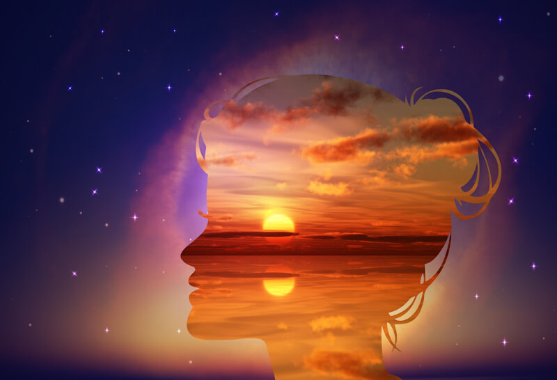 Woman head silhouette with sunset inside, universe outside as background