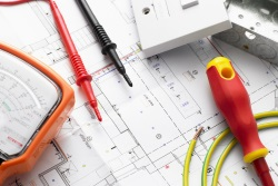 Electrician's tools laid on circuit designs