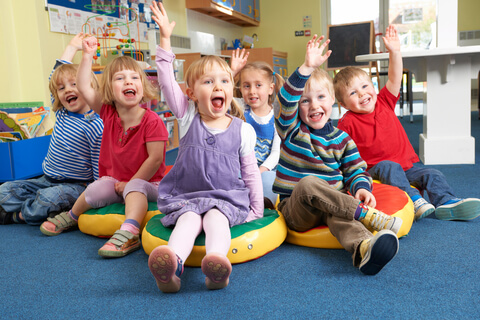 Group Of enthusiastic Children Answering Questions In Classroom