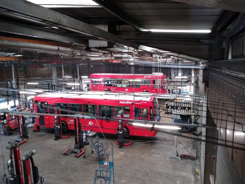 2 red buses in a factory
