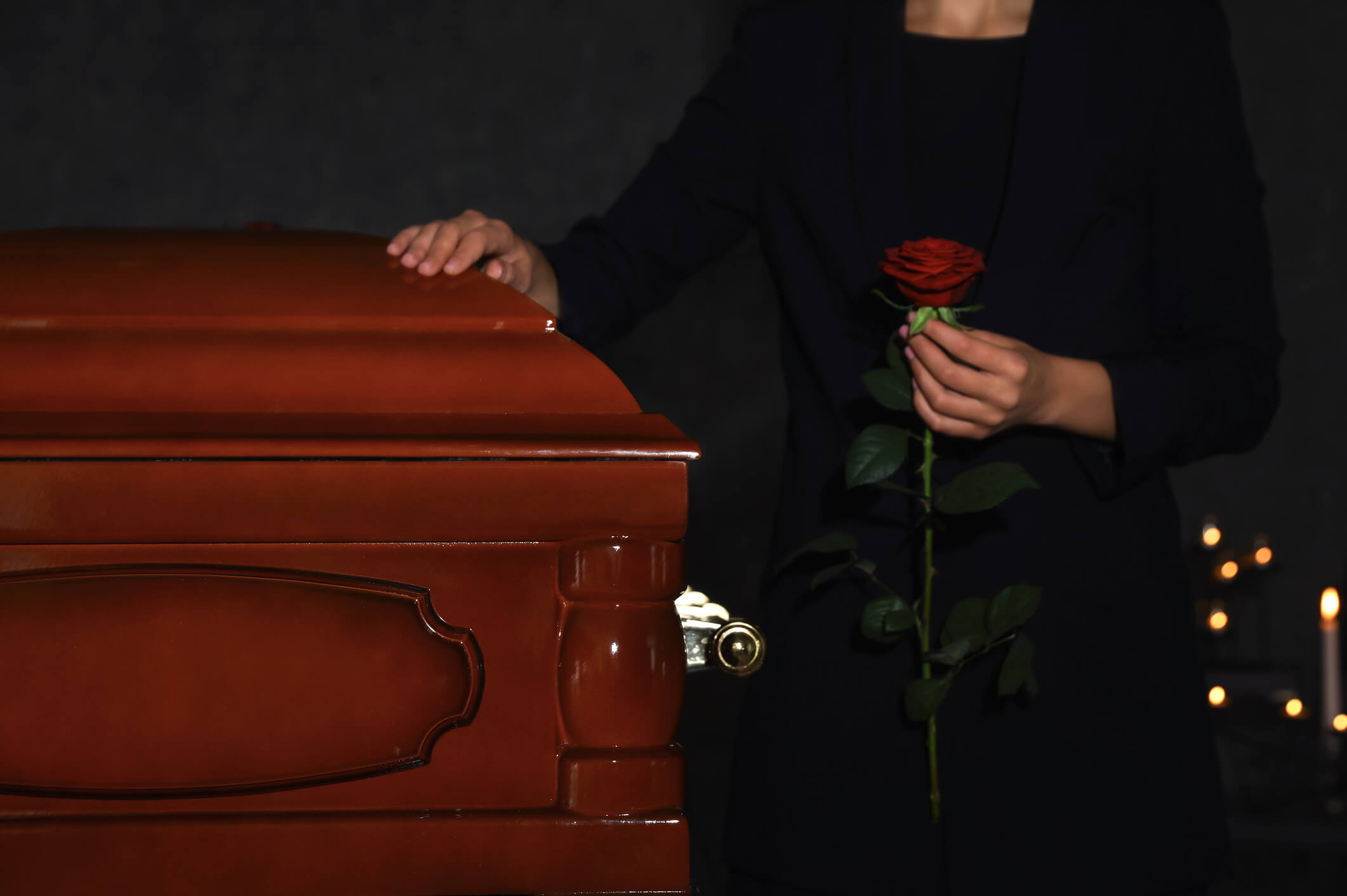 Young woman with red rose near casket in funeral home