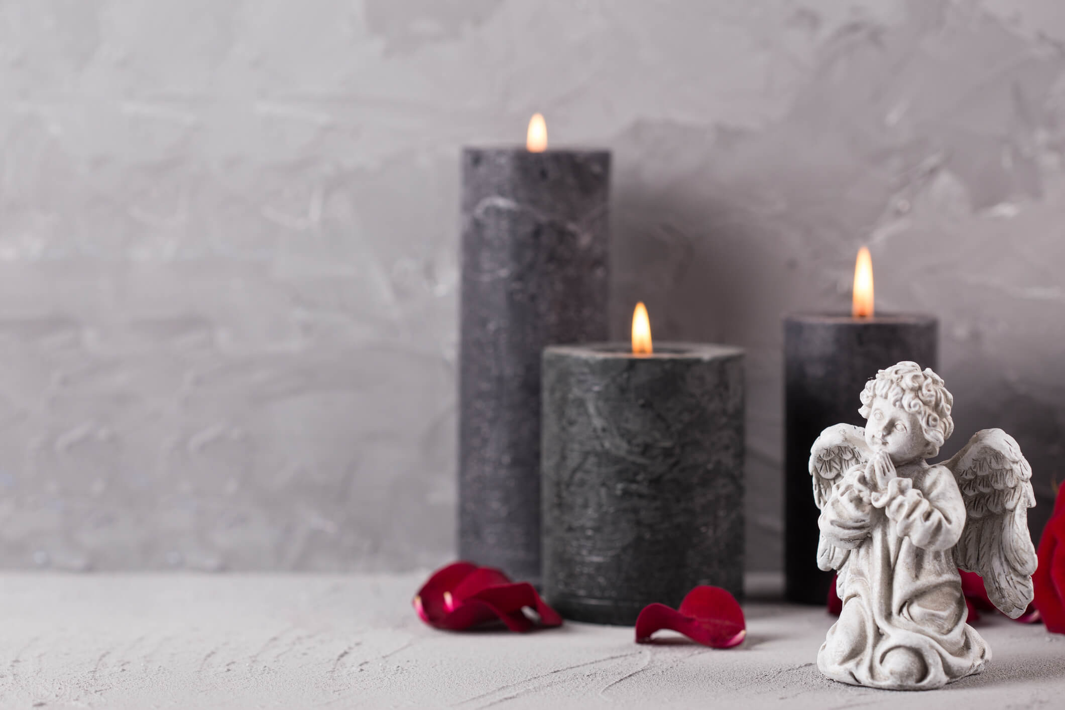 Little angel and burning candles on grey textured background