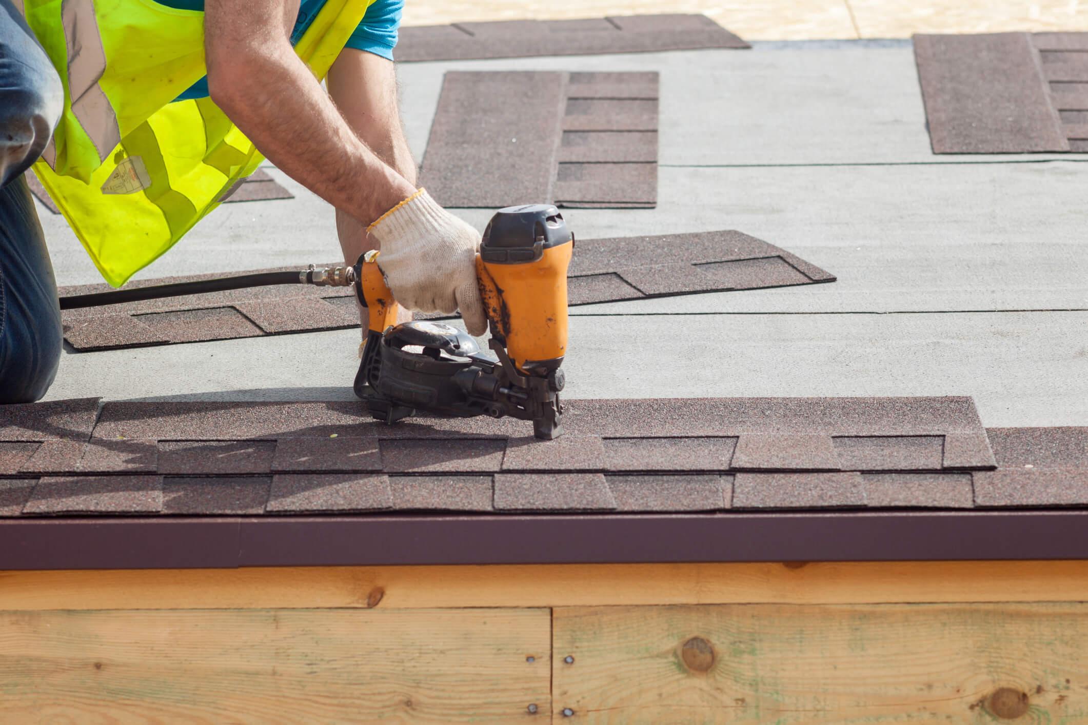 Roofer nailing tiles.