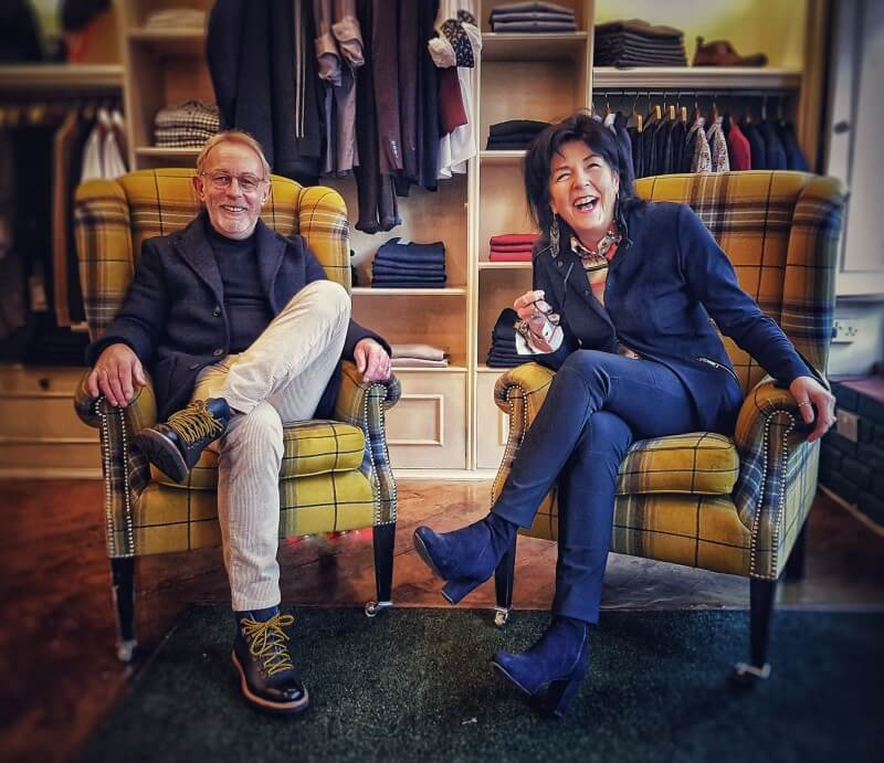 Smartly Owners Sitting on Chairs in front of top quality clothing.