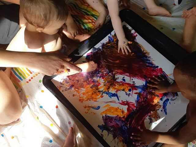 Children painting together at nursery