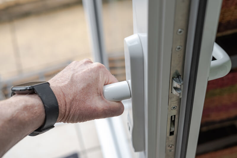 Homeowner seen gripping the handle of a newly installed uPVC high security door