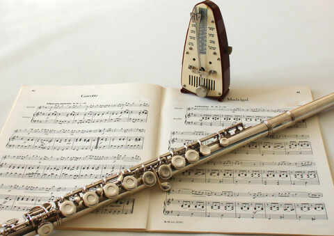 Flute sitting on Music sheets next to a metronome