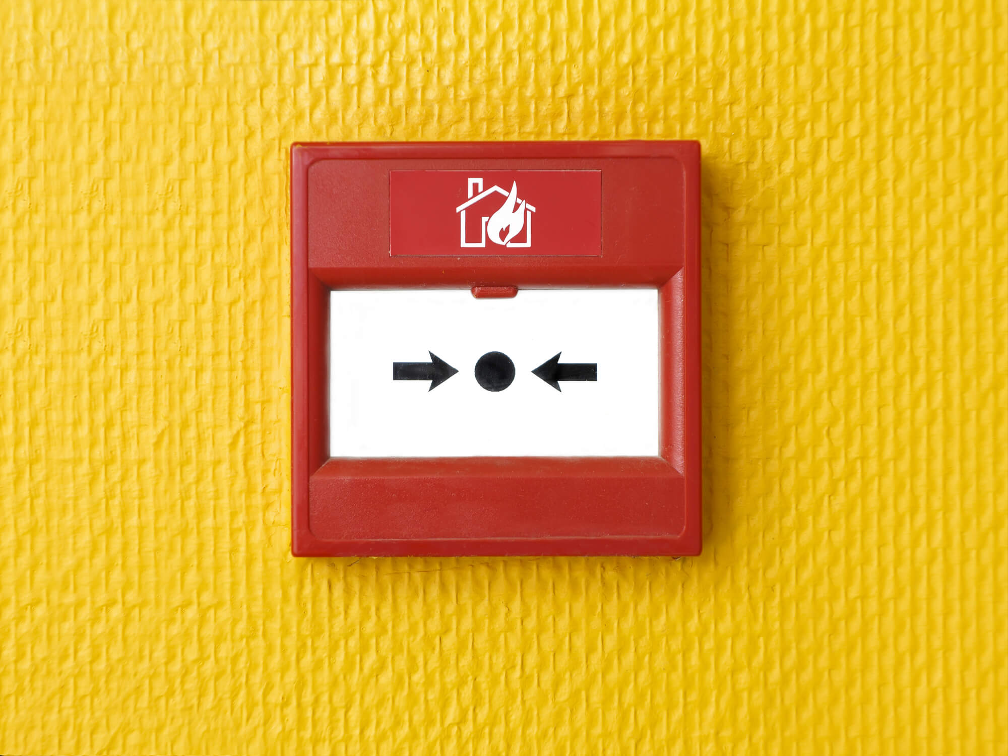 Fire Alarm on yellow wall.