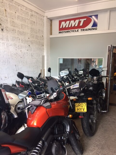 Room filled with motorcycles with MMT logo above the bikes.