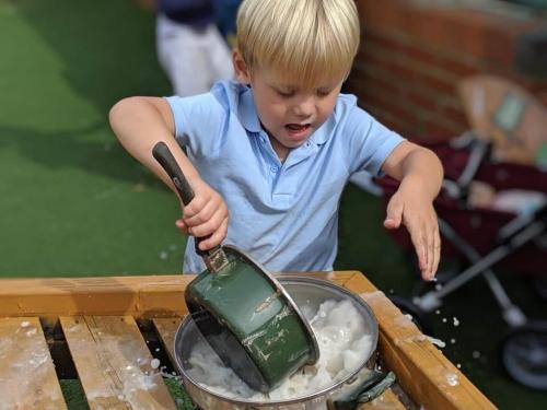 Kid washing a pan.