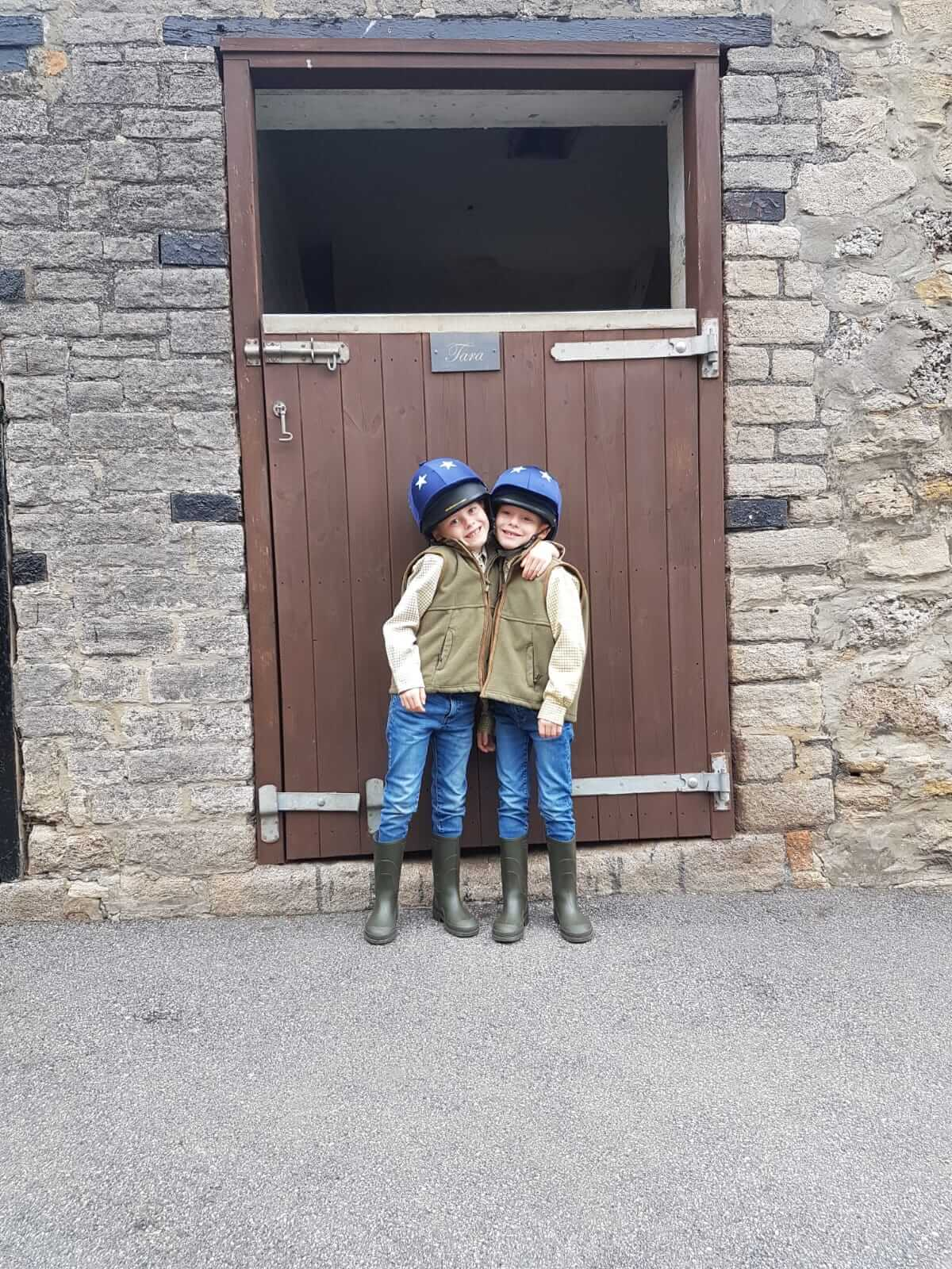 Two girls stood outside stable.