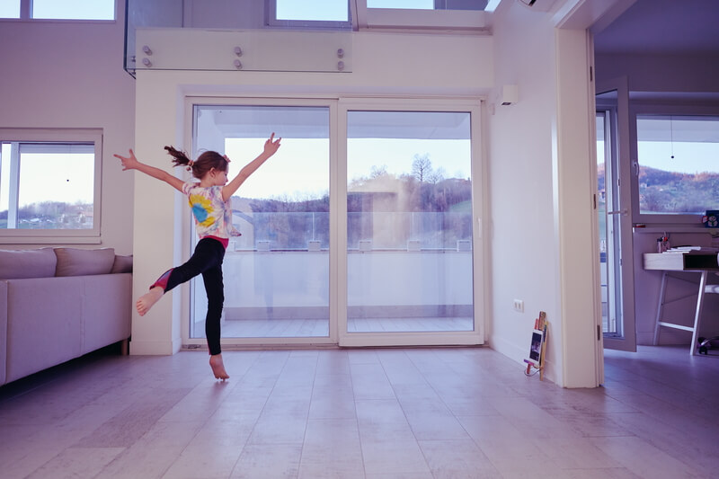 Little girl have online training over tablet and doing modern ballet dance exercise at home