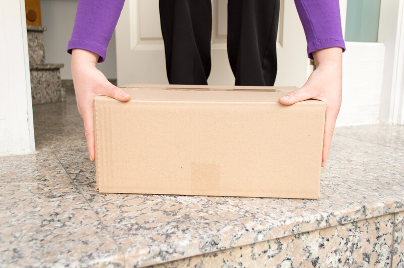 Woman picking up her delivered parcel from doorstep