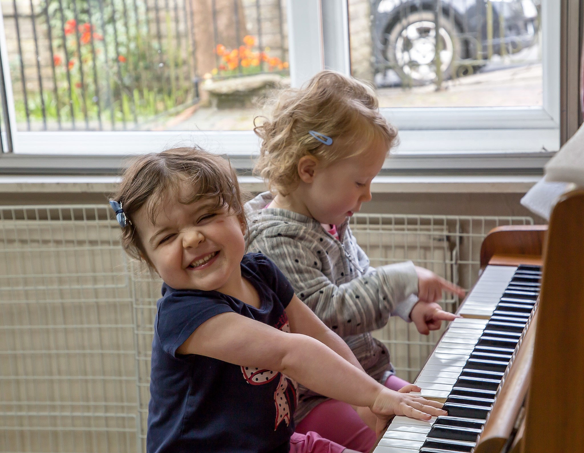 Two children playing with piano.