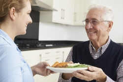 carer serving food to happy elderly man