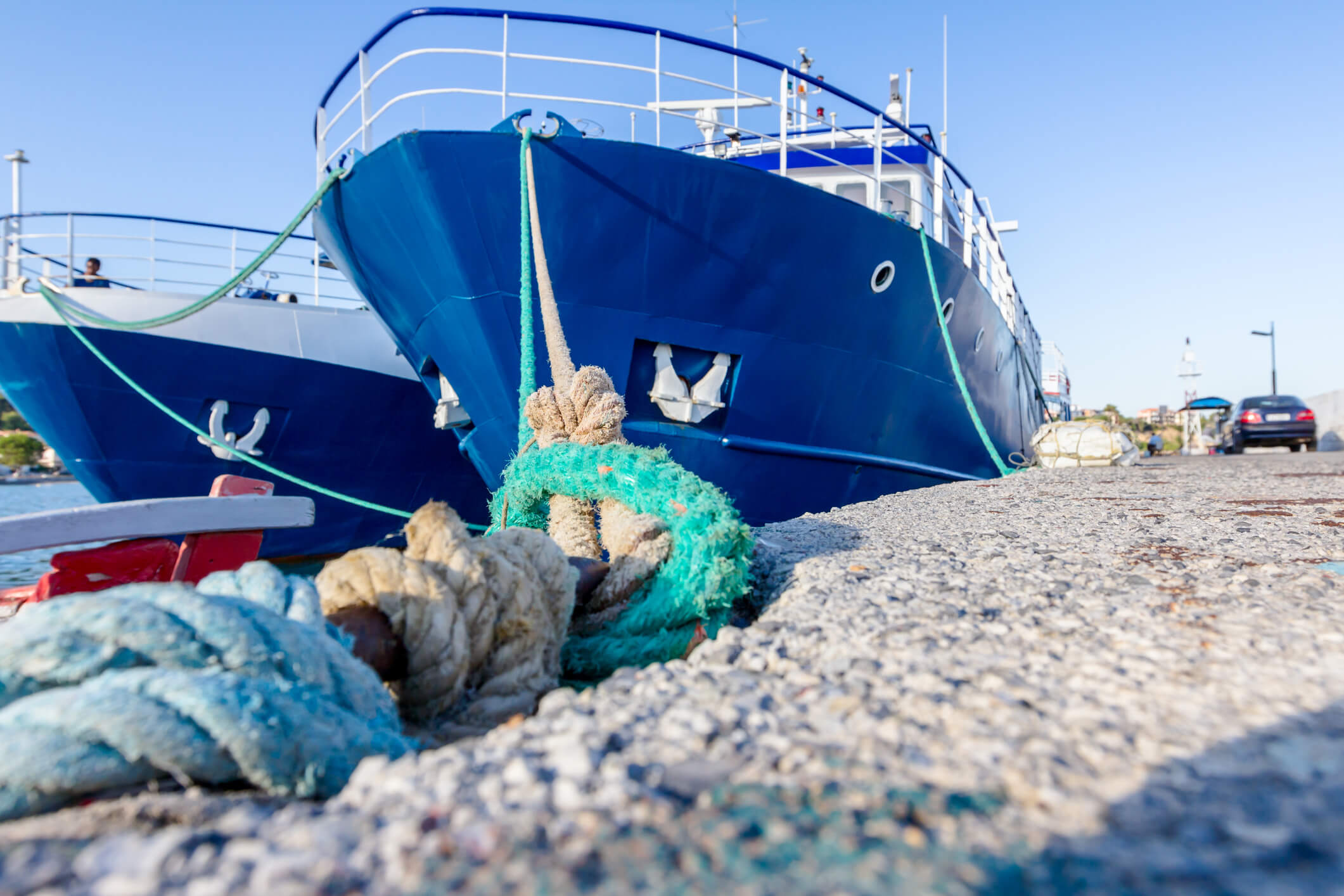 Two big fishing boats are tied up with rope for the dock, marina.