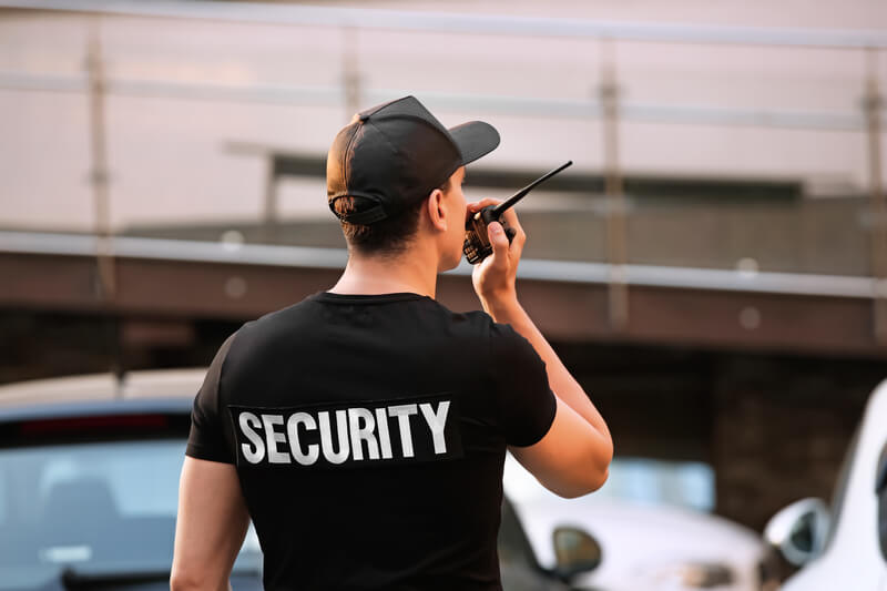 A security guard at an event talking to a collegue using a portable radio.