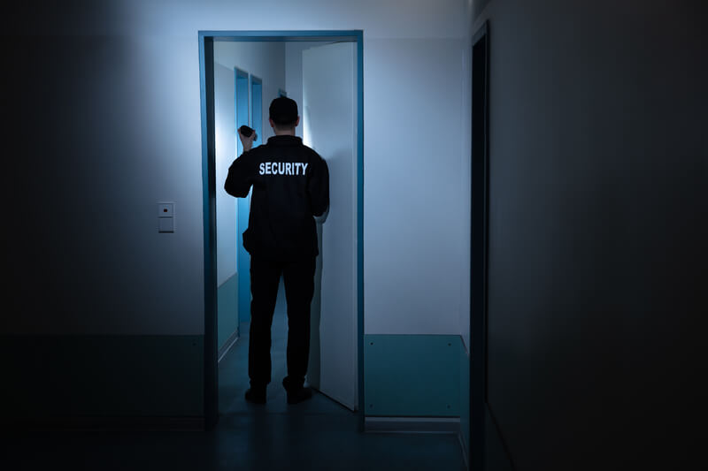 A security guard in a dark hallway with a torch.