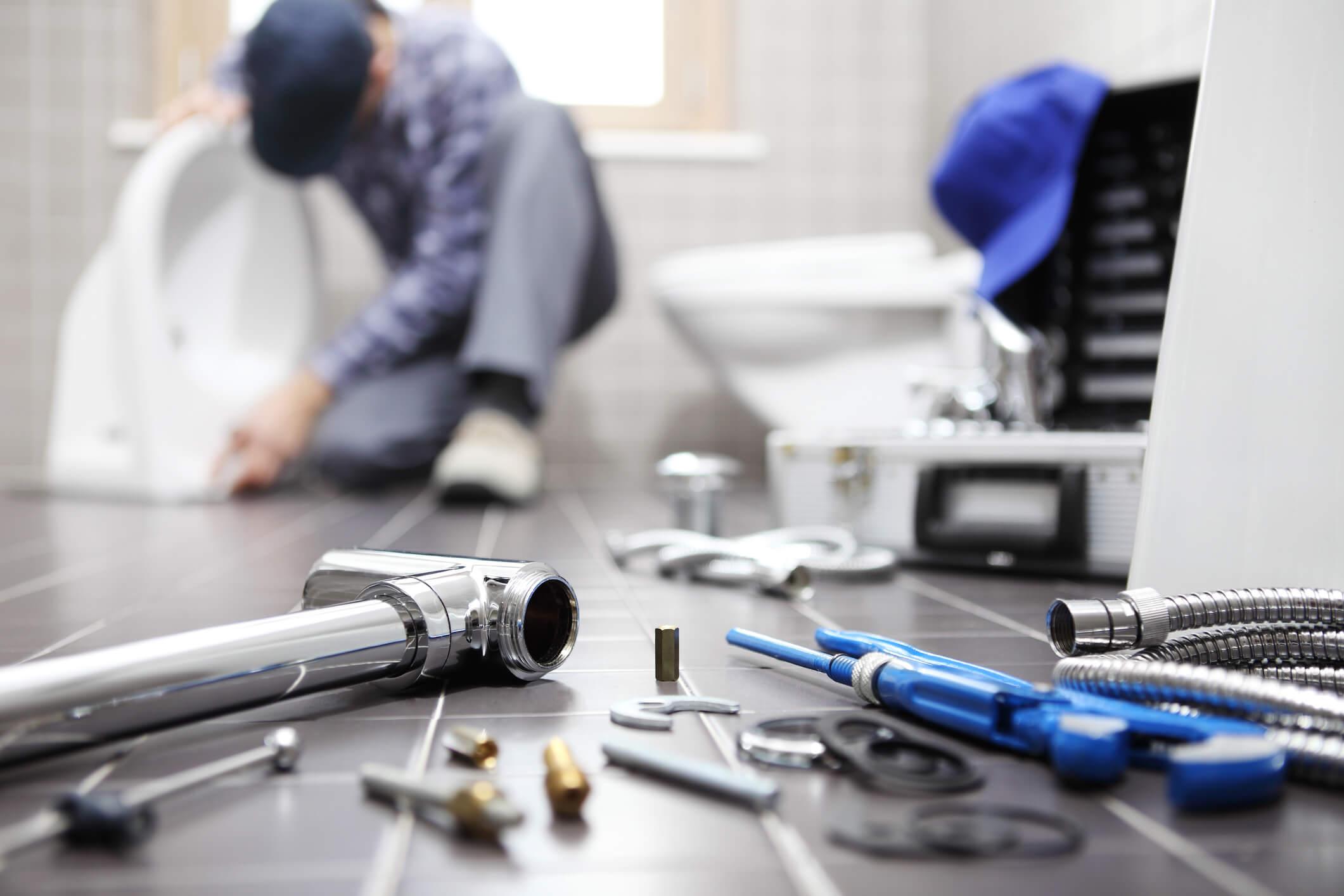 Plumber at work in a bathroom, plumbing repair service, assemble.