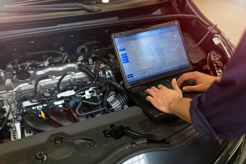 Mechanic running diagnostics laptop on car engine