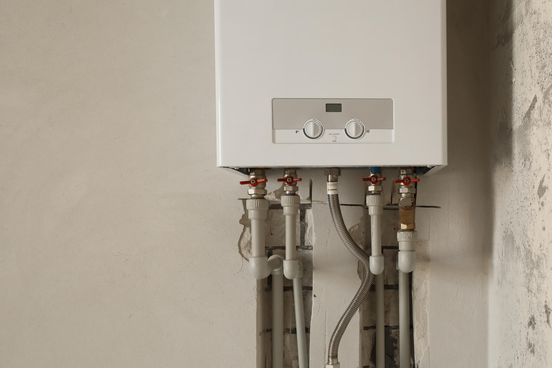 Installation of home gas heating boiler with red taps.
