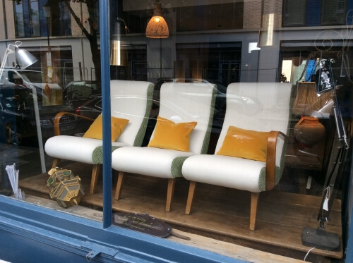 white lounge chairs with orange pillows in shop display window