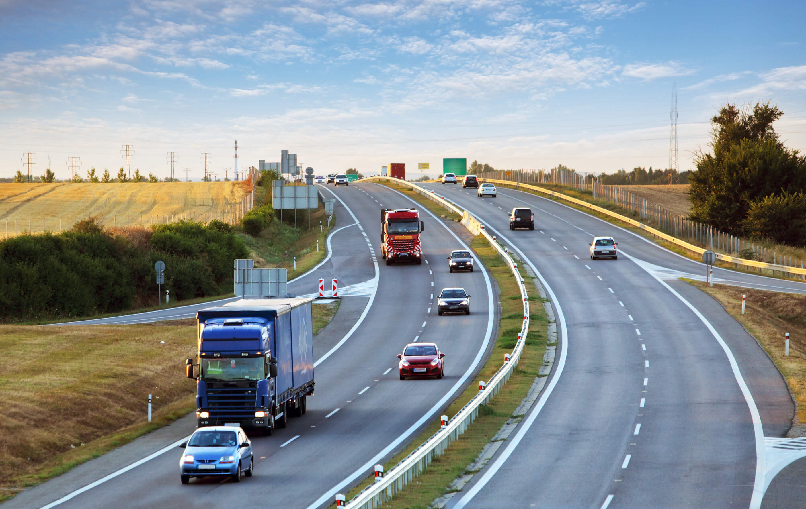 view of car and trucks driving on motorway