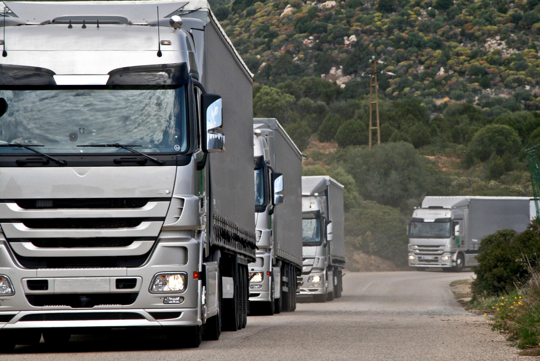 Silver trucks on long road.