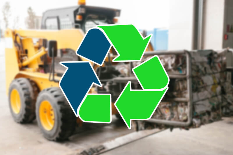 Recycling logo in front of a waste processing plant