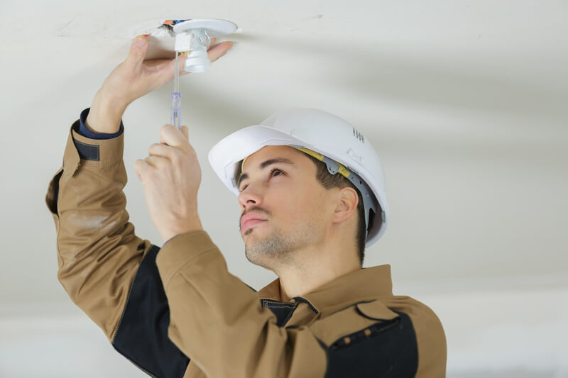 Electrician installing ceiling lights