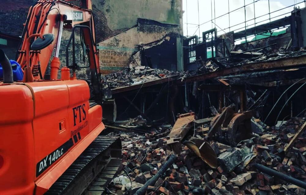 FTS Demolition LTD branded digger demolishing building
