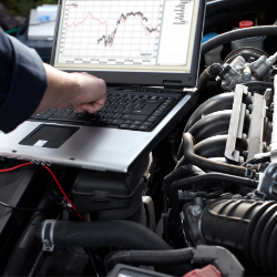 Mechanic diagnosing the cars ECU via laptop