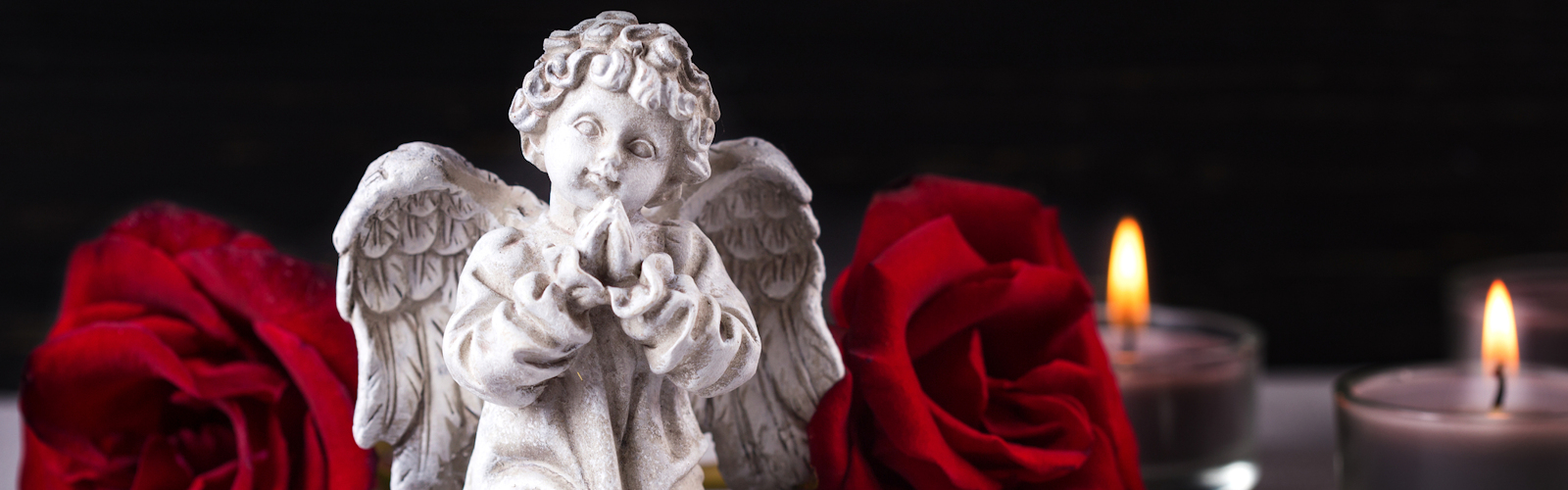 Little angel, red roses and burning candles on dark background