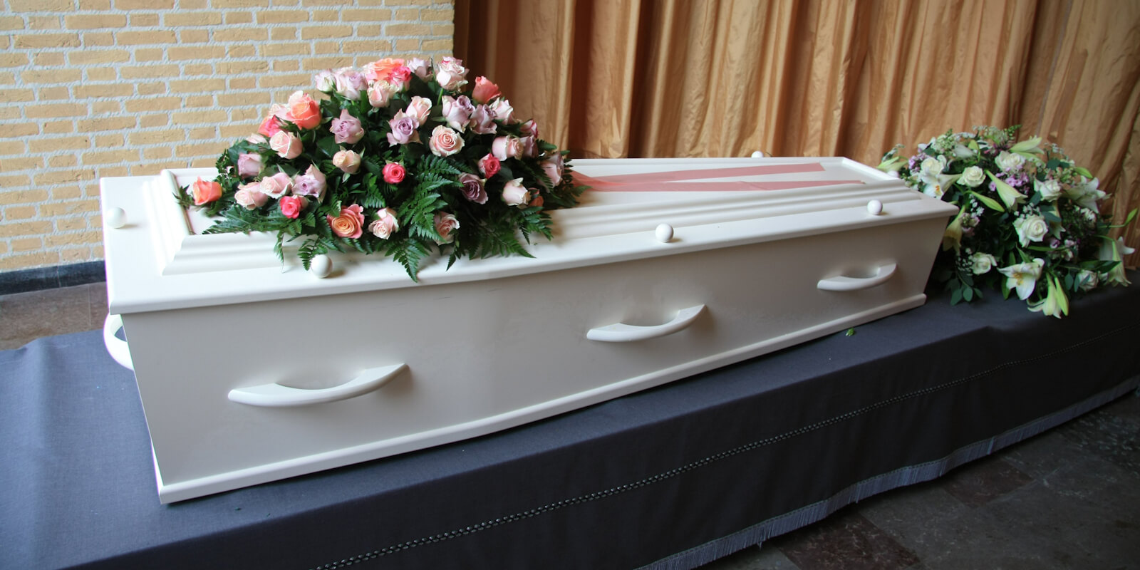 A white coffin with pink flowers at a funeral service